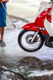 Wheel motorcycle washing with water pressure. Royalty Free Stock Photos