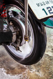 Wheel motorcycle washing with water pressure. Royalty Free Stock Photography