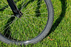 Wheel of the mountain bicycle on a green grass Royalty Free Stock Images