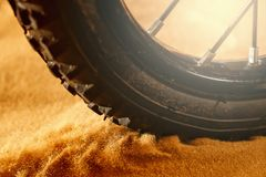 Wheel mountain bike bicycle detail in a sunny day and flying motion sand. Wheel mountain bike bicycle detail in a sunny day and flying speed motion sand Royalty Free Stock Image