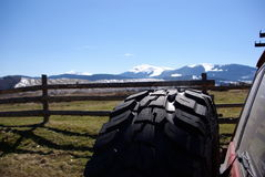 Wheel in mountains. Spare wheel on a jeep, on a background mountain peaks Stock Photo
