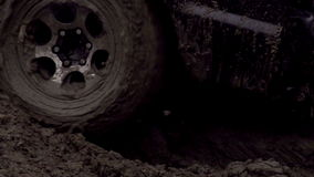 Wheel in the Mud. SUV wheel slips in the mud, but moves slowly. Slow Motion at a rate of 240 fps stock footage