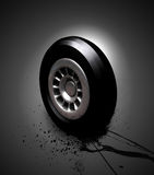 Wheel On Oil. A 3d shiny wheel/tire standing on black splashing oil Royalty Free Stock Photography