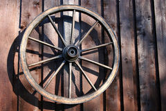Wheel of an old carriage. And its reflection on a wooden wall Royalty Free Stock Photo