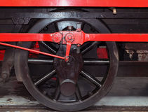 Wheel of an old steam locomotive painted black with red coupling Royalty Free Stock Photography