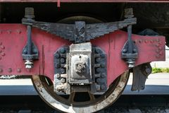 Wheel of the old steam locomotive of red color and the elements of the drive stock photos