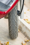 The wheel of a red moped on marble looking tiles. Royalty Free Stock Image