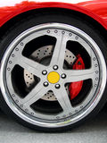 Wheel on a red sport car. Classy rim on a clean car Royalty Free Stock Images