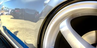 Wheel rim of a shiny white car with blue decal. Exterior of a reflective white car with blue stripe decal on the lower side. The wheel of the car has a rim royalty free stock photo