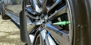 Wheel rim with silver spokes and spike. Close up shot of the wheel rim of a reflective car on a sunny day. The shiny rim has silver spokes and a single green stock photos