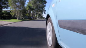 Wheel On Road 1. Low angle view of front car wheels travelling along a road and coming to a stop stock video footage