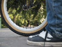 A wheel and a shoes. Focus on the bmx bicycle wheel Royalty Free Stock Image