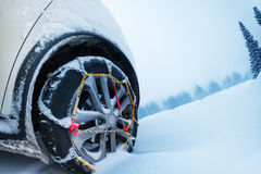 Wheel with snow tire chains on mountain road. Automobile wheel with ice tire chains on the snow-covered mountain road Royalty Free Stock Photo