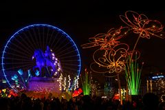 Wheel, statue and big flowers on place Bellecour. LYON, FRANCE, December 8, 2017 : Festival of the lights in Lyon. For 4 nights, different artists light up Royalty Free Stock Photo
