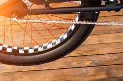 Wheel of a stylish bicycle with a black and white rim and a black rubber tire on a stylish wooden background. Wheel of a stylish bicycle with a black and white Royalty Free Stock Photos
