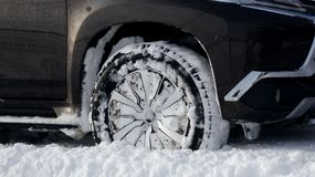 The car got stuck in the deep snow. Wheel of SUV vehicle with winter all-terrain tire in the deep snow with tread packed with snow stock photo Royalty Free Stock Image