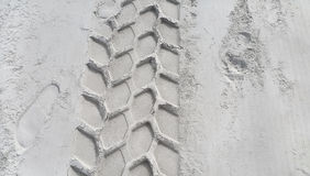Wheel track and footprints on the sand Stock Images