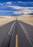 Wheel tracks in desert. Clear wheel tracks on endless desert road Royalty Free Stock Images