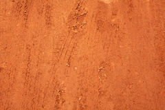 Wheel tracks on red soil rural road. Background Stock Photos