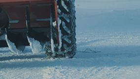 Wheel of tractor with chain on it moving in the deep snow stock video footage