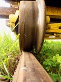 Wheel from a vintage cargo wagon. Old railway wagon of forgotten train in railway depot. Fresh green grass around rail rods Stock Images