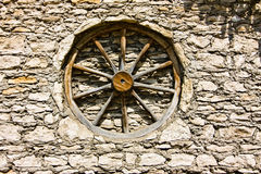 Wheel from wain in the wall. Wood wheel from wain in the brick wall Royalty Free Stock Image