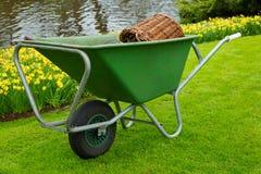 Wheelbarrel i en trädgård Fotografering för Bildbyråer