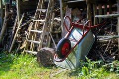 Wheelbarrow που κλίνει από πάνω σε ένα υπόστεγο με το ακατάστατο συσσωρευμένο ξύλο Στοκ φωτογραφία με δικαίωμα ελεύθερης χρήσης