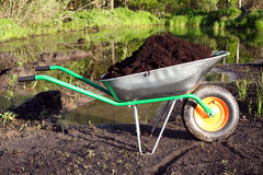 Wheelbarrow. Loaded by a ground on a lawn royalty free stock photos