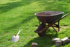 Wheelbarrow. A wheelbarrow and a shove on a grass Stock Photo