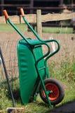 Wheelbarrow against a fence. A green wheelbarrow leaning against a fence on a farm Stock Images