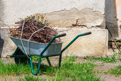 Wheelbarrow blisko starej ściany Fotografia Stock