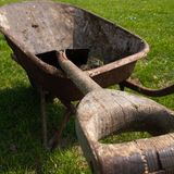 Wheelbarrow closeup. Square photo of wheel barrow in field of (green) grass. Following the line of the wooden spade invites you to start working stock image