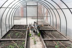 The wheelbarrow, complete with a set of old dirty garden tools under the roof in the greenhouse. Greenhouse. old dirty garden tools among the beds on the cart royalty free stock images