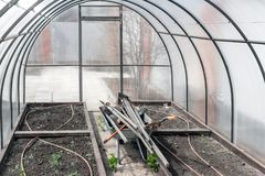 The wheelbarrow, complete with a set of old dirty garden tools under the roof in the greenhouse stock images