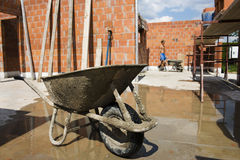Wheelbarrow on constuction site. Wheelbarrow on construction site.  Worker on background Stock Photo