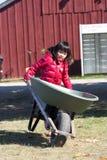 Wheelbarrow da terra arrendada da menina Fotos de Stock Royalty Free