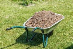 Wheelbarrow with dirt Stock Photos
