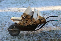 Wheelbarrow with firewood. A wheelbarrow carrying firewood in winter Stock Images