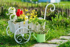 Wheelbarrow with flowers in the garden Stock Photo