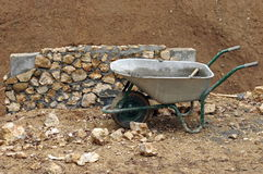 Wheelbarrow in front of a wall. In construction Stock Photo