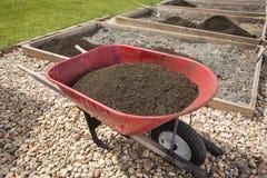 Wheelbarrow full of Compost Dirt. A wheelbarrow full of compost dirt sitting in a backyard garden ready to help grow healthy vegetables Stock Images