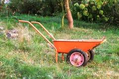 Wheelbarrow in the garden. The wheelbarrow in the garden is on the grass Royalty Free Stock Photos