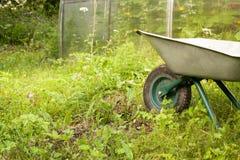 Wheelbarrow in a garden. On grass with copy space Stock Image