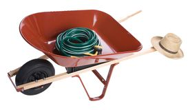 Wheelbarrow with garden hose. Red wheelbarrow with garden hose and a straw hat, isolated on white background stock photo