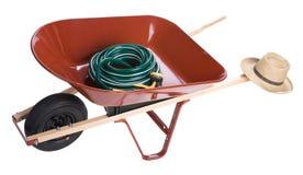 Wheelbarrow with garden hose Stock Photo