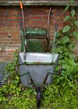 Wheelbarrow. Garden tool resting agains the wall of St Augustine's, Kilburn Royalty Free Stock Images