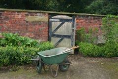 Wheelbarrow by gate Stock Photos