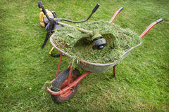 Wheelbarrow with grass and petrol trimmer Stock Images