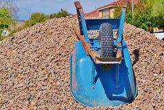 Wheelbarrow on Gravel Pile in Front of Houses Stock Photo